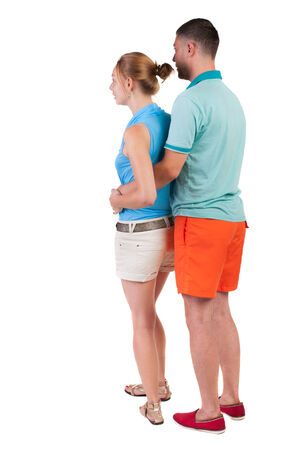 Back view of young embracing couple in shorts  hug and look. friendly girl and guy together. Rear view people collection. backside view of person.  Isolated over white background. photo