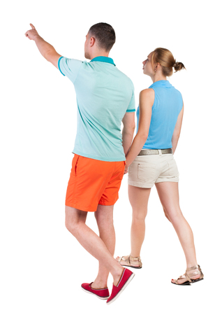 Back view of walking young couple (man and woman) pointing. going tourists in shorts considering attractions. Rear view people collection. backside view of person. Isolated over white background photo