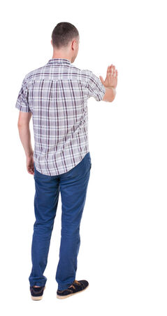 back view of man. Young man jeans presses down on something. Isolated over white background. Rear view people collection. backside view of person. she holds his hand open, palm forward photo