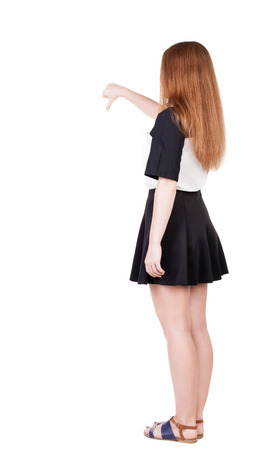 Back view of dissatisfied woman thumbs down. Rear view people collection. backside view of person. Isolated over white background. slender redhead in a dress shows hitchhiking photo