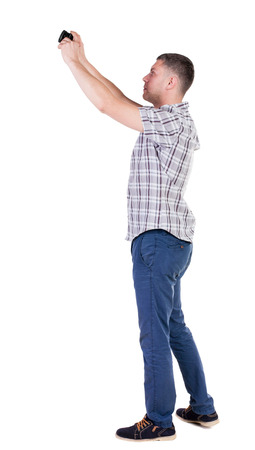 Back view of man photographing. tourist with camera. Rear view people collection.  backside view of person.  Isolated over white background. photo