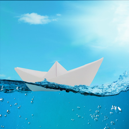 paper boat floating among the waves in the ocean. origami boat floating in the water. photo