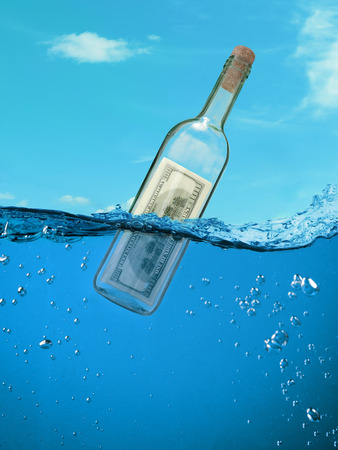 Concept  financial assistance. Bottle of money floating in the water. photo