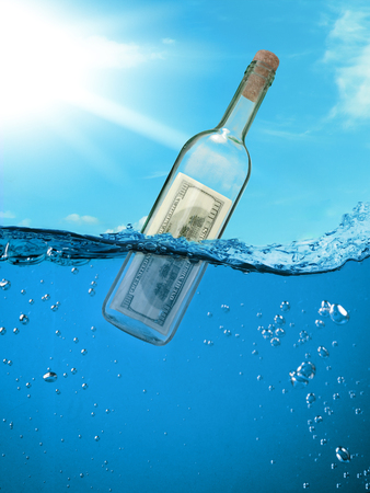 castaway: Concept  financial assistance. Bottle of money floating in the water. Stock Photo