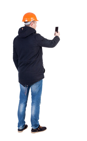 backview: Backview of an engineer in construction helmet stands and using a mobile phone. Standing young guy. Rear view people collection.  backside view of person.  Isolated over white background.
