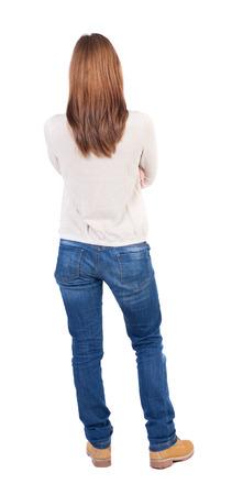 espalda: vista trasera de la mujer hermosa joven de pie en pantalones vaqueros. ni�a mirando. Vista posterior recogida de las personas. backside vista de la persona. Aislado sobre fondo blanco. Foto de archivo