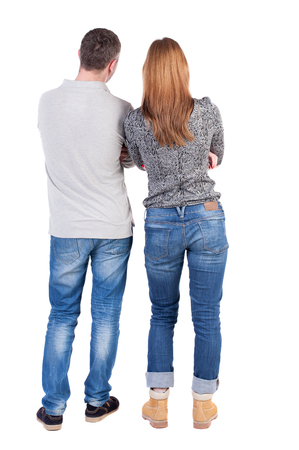 red jeans: Back view of young embracing couple (man and woman) hug and look into the distance. beautiful friendly girl and guy together. Rear view people collection.  backside view of person.  Isolated over white background. Stock Photo