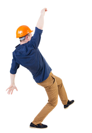hombre cayendo: Equilibrio joven. o esquivar al hombre que cae. trabajador de la construcción del casco se cae. Vista posterior recogida de las personas. backside vista de la persona. Aislado sobre fondo blanco.