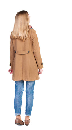 back view of standing young beautiful  blonde woman in brown cloak. girl  watching. Rear view people collection.  backside view of person.  Isolated over white background. photo