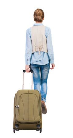 back view of walking  woman  with suitcase. beautiful girl in motion.  backside view of person.  Rear view people collection. Isolated over white background. girl takes a big suitcase on wheels photo