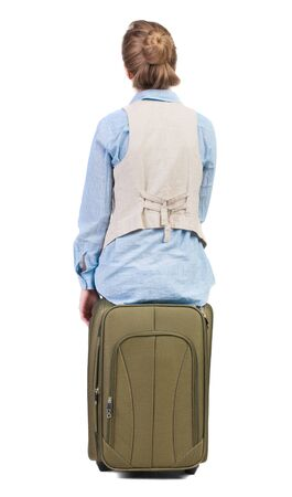back view of woman  in vest sits on a suitcase. beautiful  girl in motion.  backside view of person.  Rear view people collection. Isolated over white background. photo