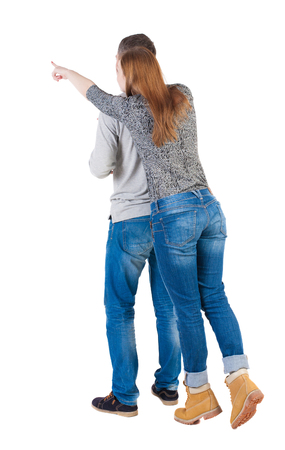 tiptoes: young couple pointing at wal Back view  (woman and man). Rear view people collection. She stood on tiptoes shows something in front of a hand.