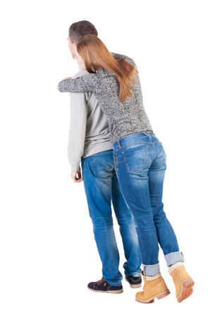 tiptoes: Back view of young embracing couple (man and woman) hug and look into the distance. beautiful friendly girl and guy together. Rear view people collection.  backside view of person.  Isolated over white background. Girl standing on tiptoes and hugs from be Stock Photo