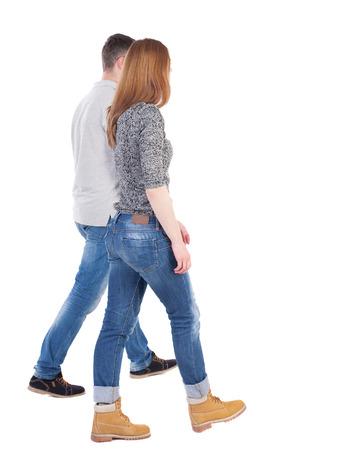 caminando: Volver la vista va pareja. caminar chica amable y chico tomados de la mano. Vista posterior recogida de las personas. backside vista de la persona. Aislado sobre fondo blanco. Hombre con estilo y mujer van juntos.