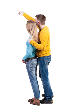 woman behind: young couple pointing at wal Back view  (woman and man). Rear view people collection.  backside view of person.  Isolated over white background. The guy in the yellow sweater hugging behind her and shows her something interesting in the sky. Stock Photo