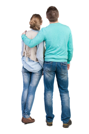 man in jeans: Back view of young embracing couple (man and woman) hug and look into the distance. beautiful friendly girl and guy together. Rear view people collection.  backside view of person.  Isolated over white background. Guy hugs the girl in the shoulder vest.