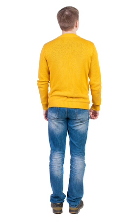 back view of man: Back view of man in jeans. Standing young guy. Rear view people collection.  backside view of person.  Isolated over white background. The guy in the yellow jacket is hands down along the body. Stock Photo