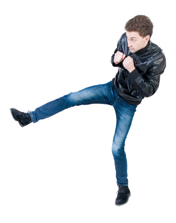 wimp: skinny guy funny fights waving his arms and legs. Isolated over white background. The boy timidly is kicked.