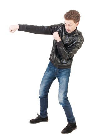 wimp: skinny guy funny fights waving his arms and legs. Isolated over white background. Man shoots with his right hand. Stock Photo