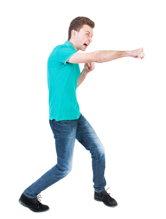 wimp: skinny guy funny fights waving his arms and legs. Isolated over white background. Funny guy clumsily boxing. Clumsily fighting man in a green jacket.