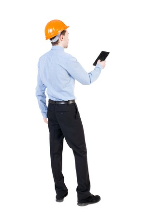 backview: Backview of business man in construction helmet stands and enjoys tablet or using a mobile phone. Standing young guy. Rear view people collection.  backside view of person.  Isolated over white background. Businessman supervises construction. Stock Photo
