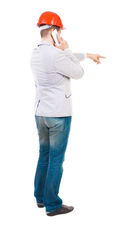 backview: Backview of business man in construction helmet stands and enjoys tablet or using a mobile phone. Standing young guy. Rear view people collection.  backside view of person.  Isolated over white background. Young businessman gives instructions on the phone