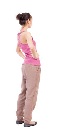 slacks: back view of standing young beautiful  woman.  girl  watching. Rear view people collection.  backside view of person.  Isolated over white background. African-American woman in brown slacks put his hands on the belt. Stock Photo