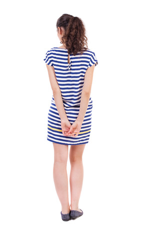 behind: back view of standing young beautiful  woman.  girl  watching. Rear view people collection.  backside view of person.  Isolated over white background. African-American in the summer striped dress modestly holding hands behind his back.