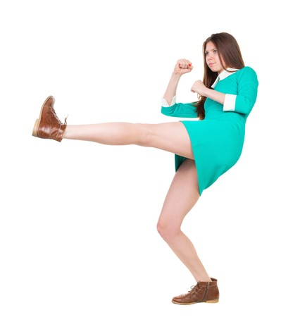 wimp: skinny woman funny fights waving his arms and legs. Isolated over white background. The girl in a dress beats foot in brown shoe. Stock Photo