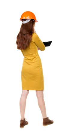 backview: Backview of business woman in construction helmet stands and enjoys tablet or using a mobile phone. Standing young girl. Rear view people collection.  backside view of person.  Isolated over white background. Girl dress in mustard works on a computer. Stock Photo