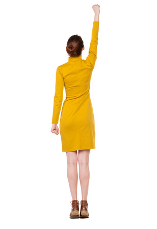 Back view of  woman.  Raised his fist up in victory sign.  Rear view people collection.  backside view of person.  Isolated over white background. Girl in a mustard-colored dress standing in a pose superhero photo