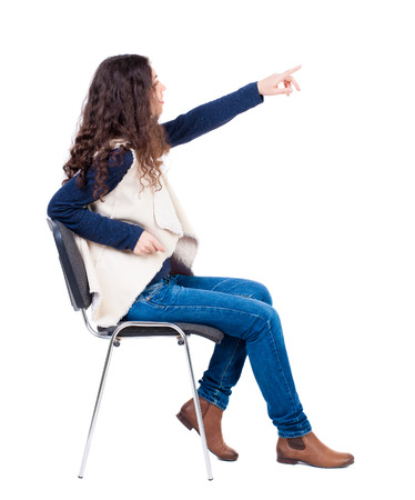 back view of young beautiful  woman sitting on chair and pointing.  girl  watching. Rear view people collection.  backside view of person.  Isolated over white background. Stock Photo