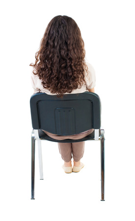 back view of young beautiful  woman sitting on chair.  girl  watching. Rear view people collection.  backside view of person.  Isolated over white background. Standard-Bild