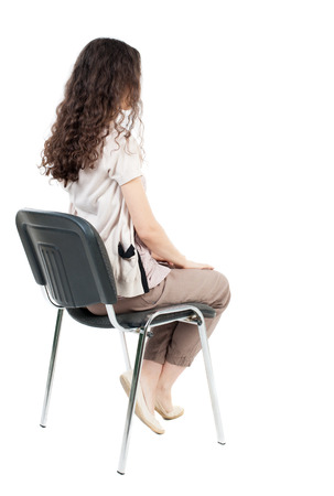 from side: back view of young beautiful  woman sitting on chair.  girl  watching. Rear view people collection.  backside view of person.  Isolated over white background. Stock Photo