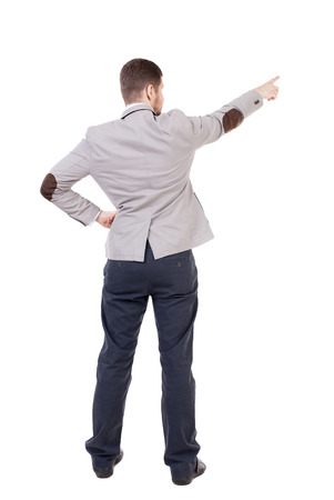 powerfully: Back view of pointing business man. gesticulating young guy in black suit. Rear view people collection.  backside view of person.  Isolated over white background. office worker in a shirt and trousers powerfully indicates something Side. putting his hand