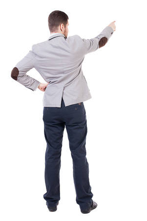 powerfully: Back view of pointing business man. gesticulating young guy in black suit. Rear view people collection.  backside view of person.  Isolated over white background. office worker in a shirt and trousers powerfully indicates something Side. Man wearing trous