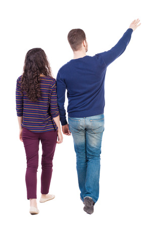 Back view of walking young couple (man and woman) pointing. Rear view people collection. backside view of person. Isolated over white background. Bearded man and curly girl go and look to the side.