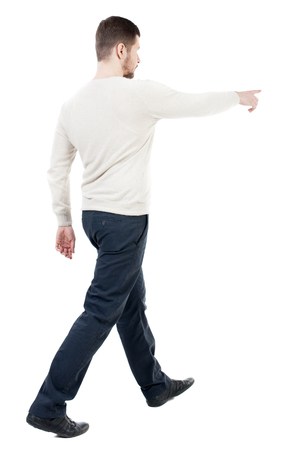 Back view of going  handsome man in jeans pointing. walking young guy . Rear view people collection.  backside view of person.  Isolated over white background. Man approaching the object shows up on him. Stock Photo