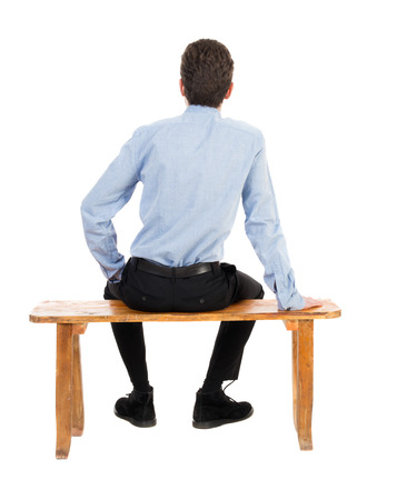 from side: back view of business man sitting on chair.  businessman watching. Rear view people collection.  backside view of person.  Isolated over white background. Businessman resting on a park bench Stock Photo
