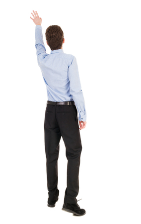 powerfully: Back view of pointing business man. gesticulating young guy in black suit. Rear view people collection.  backside view of person.  Isolated over white background. office worker in a shirt and trousers powerfully indicates something Side. Businessman accom Stock Photo