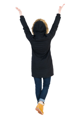parka: Back view of Beautiful woman in parka looking at wall and Holds  hand up.