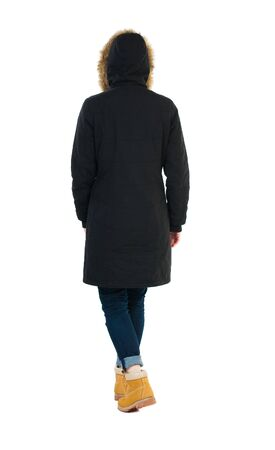 treading: Back view of going  woman in parka.