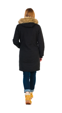 woman behind: Back view of going  woman in parka.