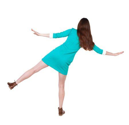 balances: Back view woman Balances waving her arms.    Stock Photo