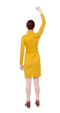 Back view of  woman.  Raised his fist up in victory sign.  Rear view people collection.  backside view of person.  Isolated over white background. Girl in mustard strict dress showing gesture of joy. photo