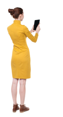 back view of standing young beautiful  girl with tablet computer in the hands of. girl  watching. Rear view people collection.  backside view of person.  Isolated over white background. Girl in mustard strict dress looks into a tablet.