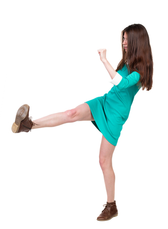 wimp: skinny woman funny fights waving his arms and legs. Isolated over white background. The girl in a green dress standing sideways strict and swings his left foot.