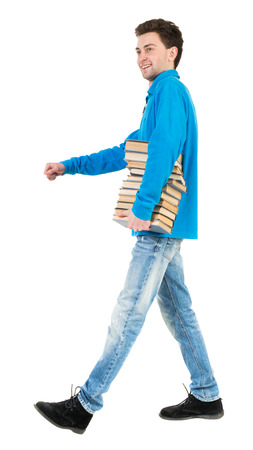 treading: Back view of going  handsome man carries a stack of books. walking young guy . Rear view people collection.  backside view of person.  Isolated over white background. Satisfied smiling senior carries books from the library.
