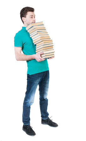 striding: Back view of going  handsome man carries a stack of books. walking young guy . Rear view people collection.  backside view of person.  Isolated over white background. High school student standing with his chin a stack of books. Stock Photo