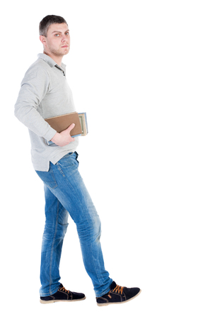 treading: Back view of going  handsome man carries a stack of books. walking young guy . Rear view people collection.  backside view of person.  Isolated over white background. A guy with a small stack of books out into the distance. students with books going and l Stock Photo